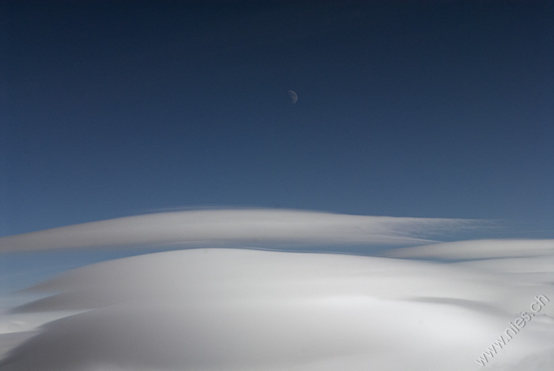 Moon above lenticular clouds