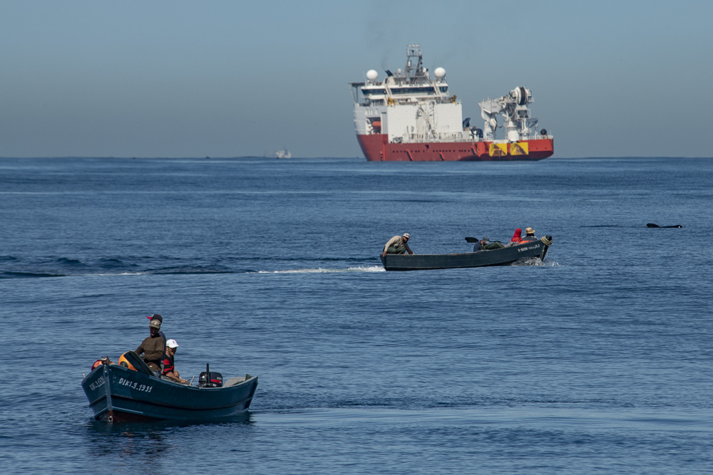 Moroccan fishermen and cargo ship
