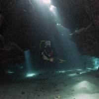 Cave Diver with Light Beams